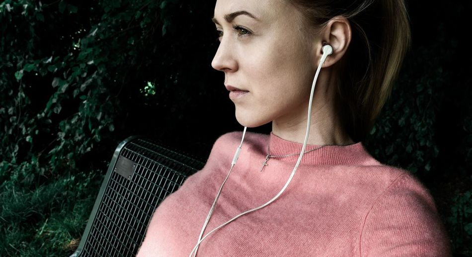 Close-up of thoughtful woman listening to music through in-ear headphones