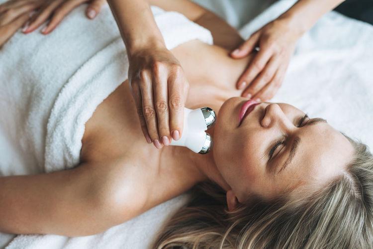 Young blonde woman enjoys facial massage with microcurrent facial massager