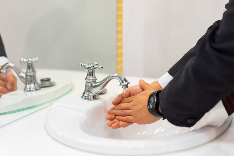 Close-up of businessman washing hands at bathroom
