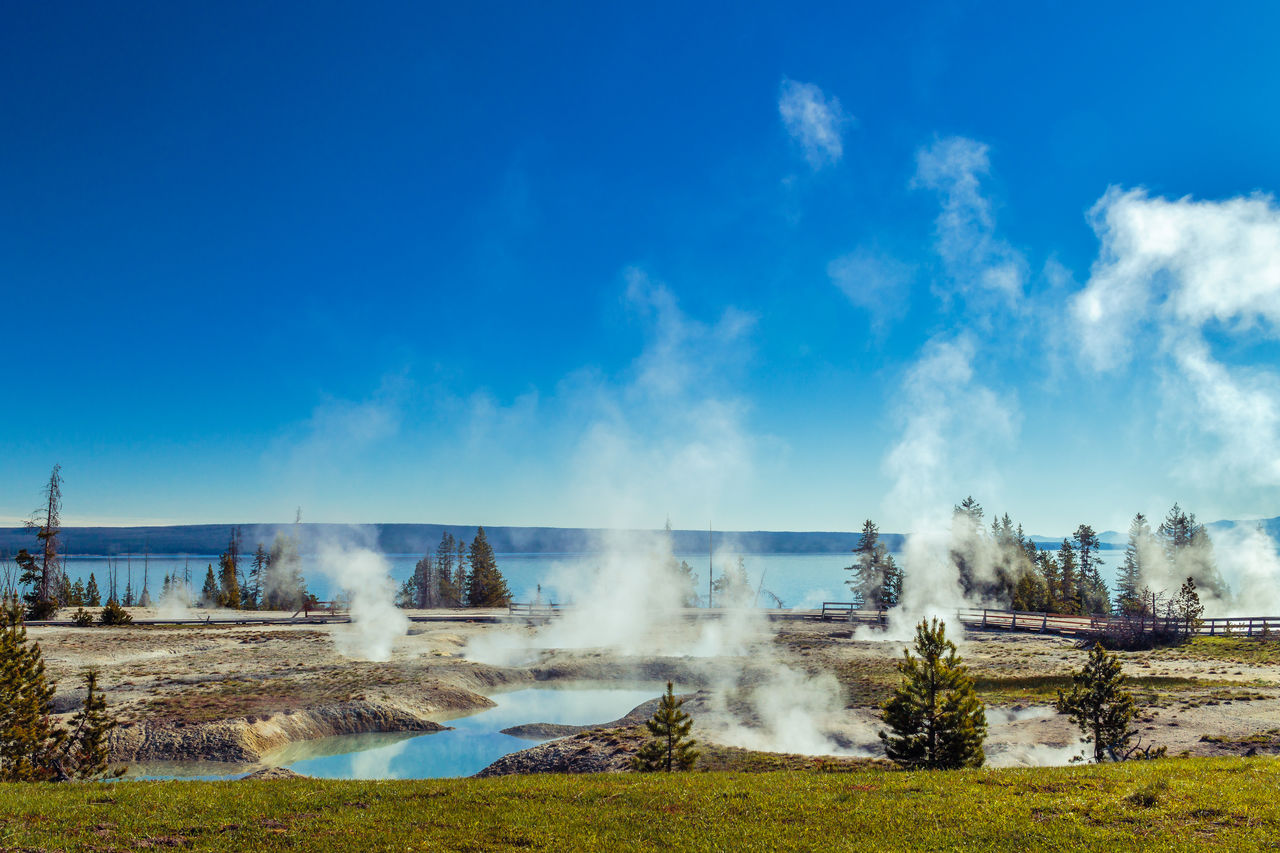 Steam Emitting From Hot Springs Against Sky