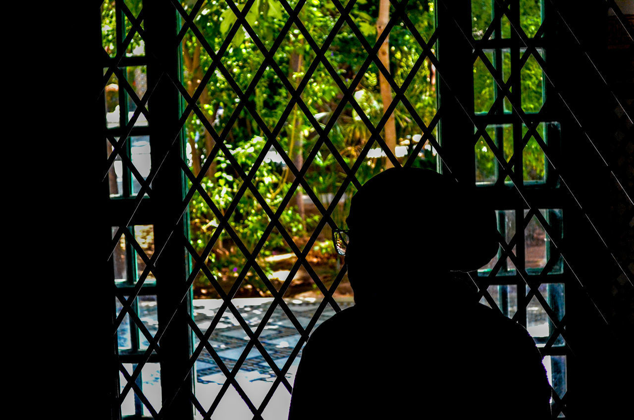 REAR VIEW OF SILHOUETTE MAN LOOKING THROUGH METAL FENCE