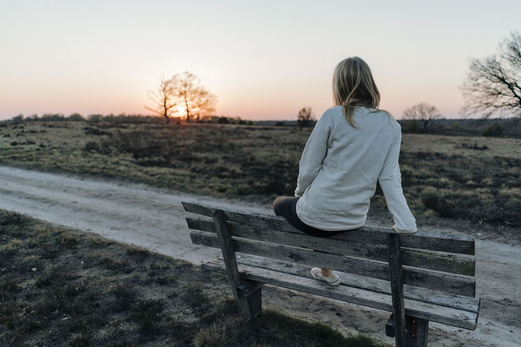 Rear view of woman sitting on bench on field against sky