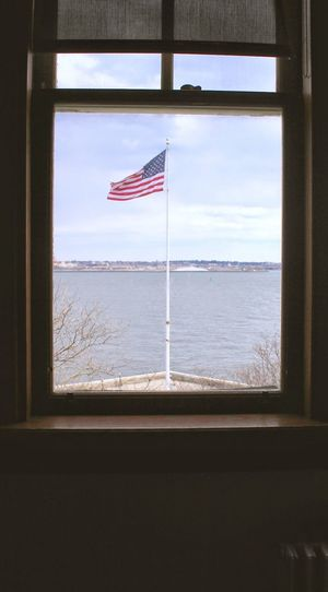 Solitary American Flag viewed from the Immigrant Building, Ellis Island, NY Window Patriotism Flag Politics And Government
