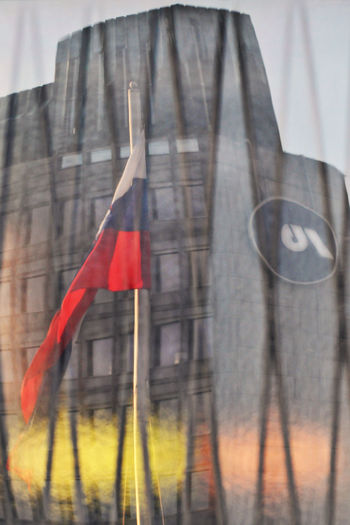 Close-up of red flag hanging on glass