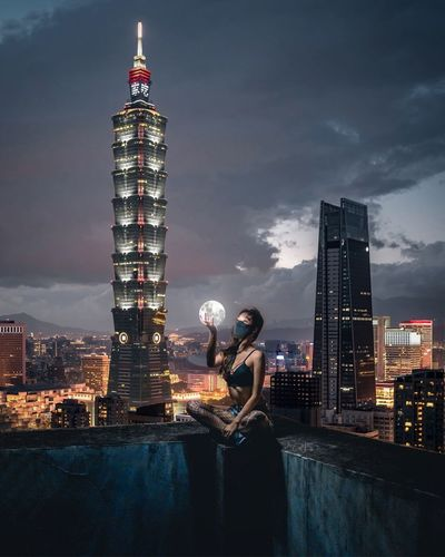 Illuminated tower amidst buildings in city against sky