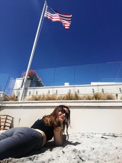 Portrait of woman lying at beach with american flag in background against clear blue sky