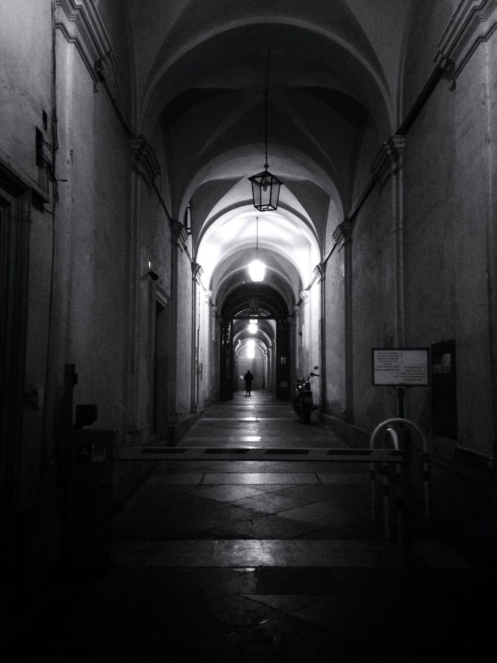 indoors, the way forward, diminishing perspective, architecture, corridor, built structure, arch, empty, vanishing point, narrow, transportation, tunnel, building, long, illuminated, absence, in a row, ceiling, no people, lighting equipment