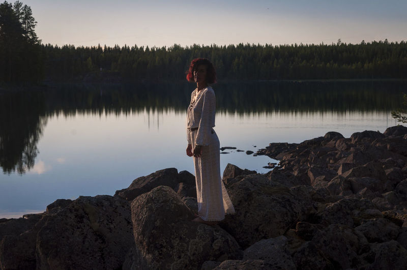 Woman Standing On Rock By Lake During Sunset