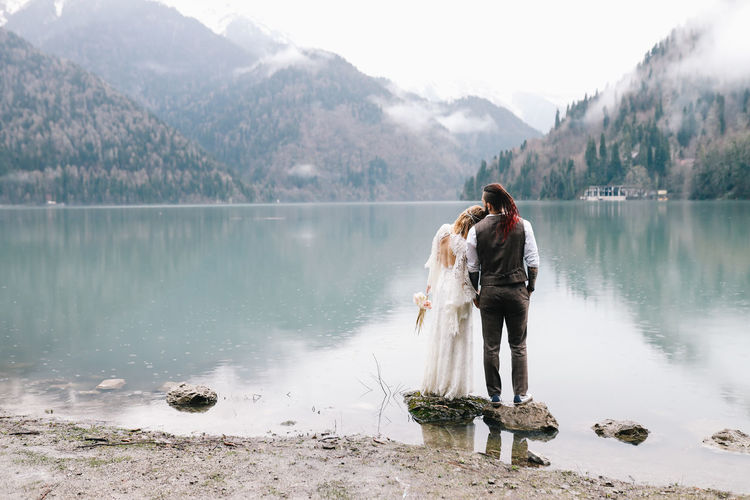A happy couple in love and married embrace in nature by the lake and the misty mountains