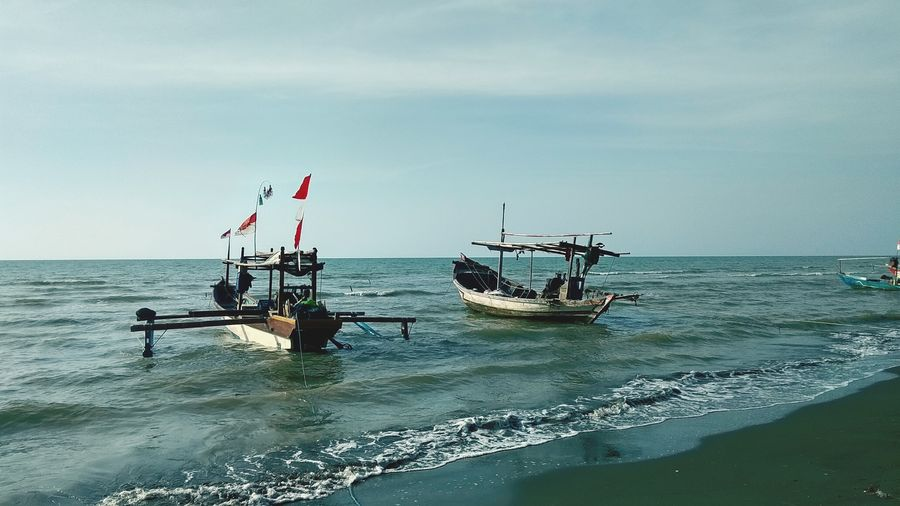 Fishing boats on sea against sky