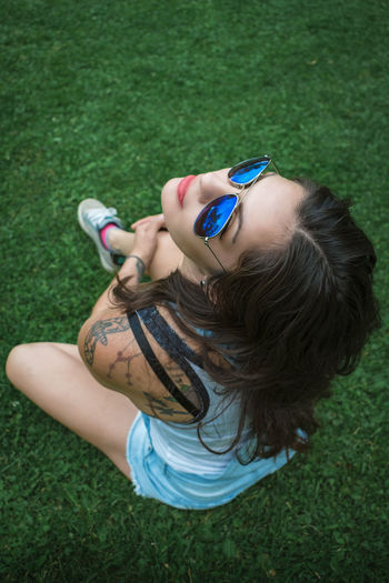High angle view of beautiful woman wearing sunglasses while sitting on grassy field