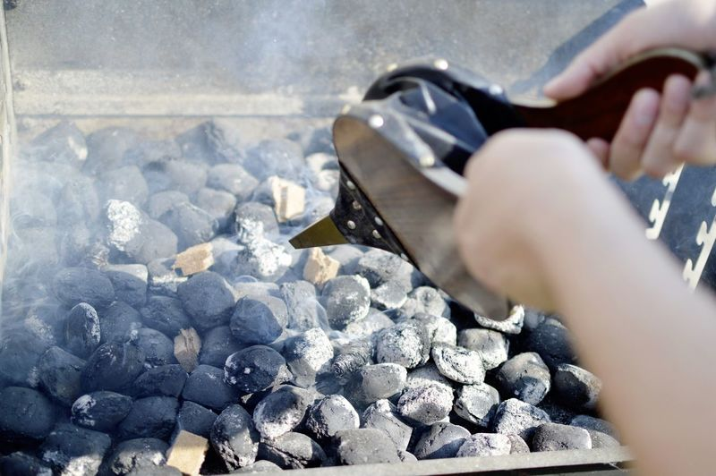 Cropped Image Of Person Cooking Over Barbecue Grill