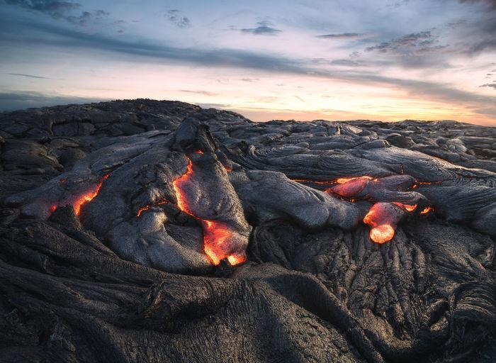Bonfire on rock against sky during sunset