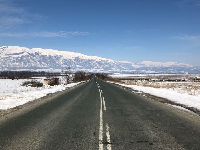 Road Amidst Snow Covered Mountain Against Sky