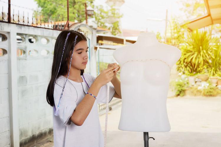 Girl measuring dressmaker model with tape measure at workshop