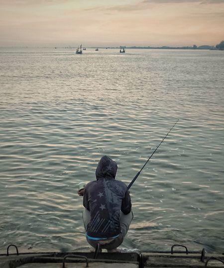 Rear view of man fishing in sea against sky