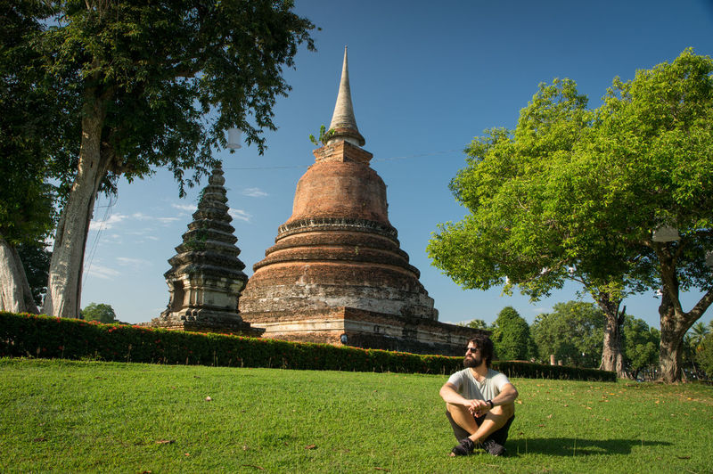 Ancient temples in sukhothai Plant Tree Grass Architecture Built Structure Nature Religion Building Exterior Sky Green Color Place Of Worship Spirituality Day One Person Building Real People Sitting Casual Clothing Belief Outdoors Thailand Buddha Buddhist Temple