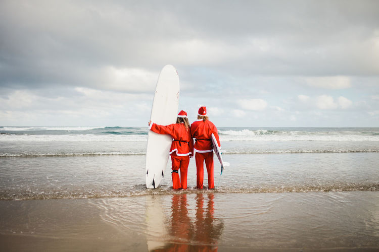 Rear view of couple wearing santa costumes holding surfboards in sea