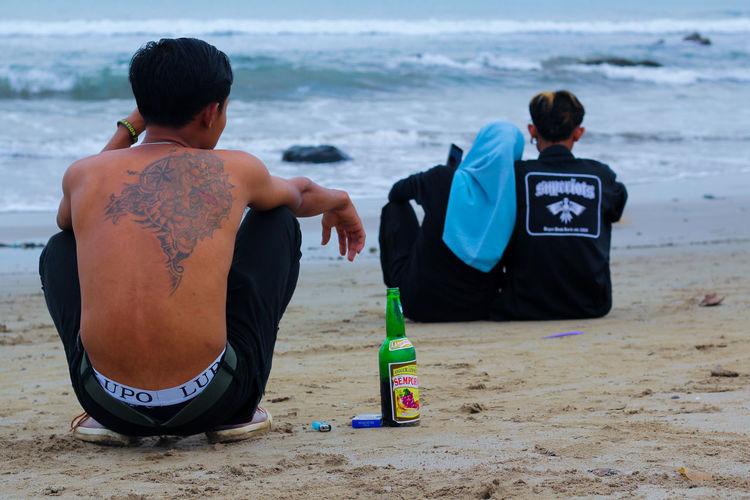 Rear view of men sitting on beach