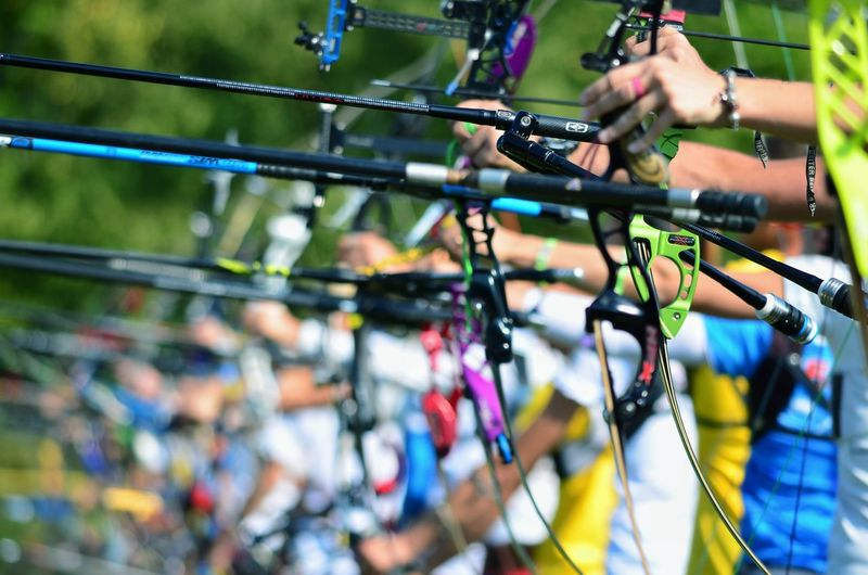 People aiming with bows during competition