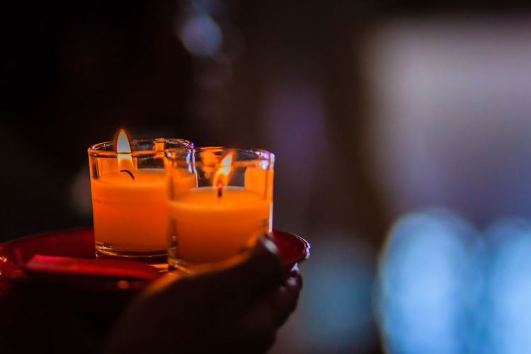 Close-up of hand holding candles in plate
