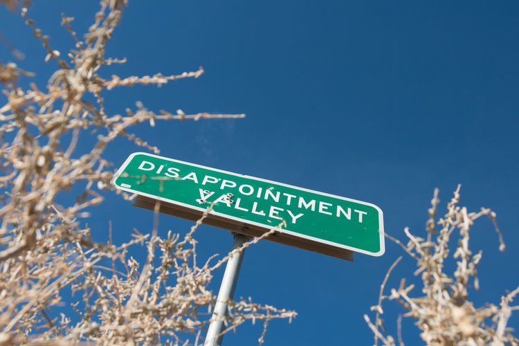 The road sign with bullet holes in Disappointment Valley, Colorado. Someone was overwhelmed by disappointment it would seem. Bullet Holes Day Disappointment Low Angle View Outdoors Rural Signs