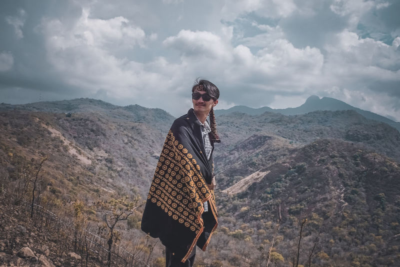 Man wearing sunglasses standing on mountain against sky