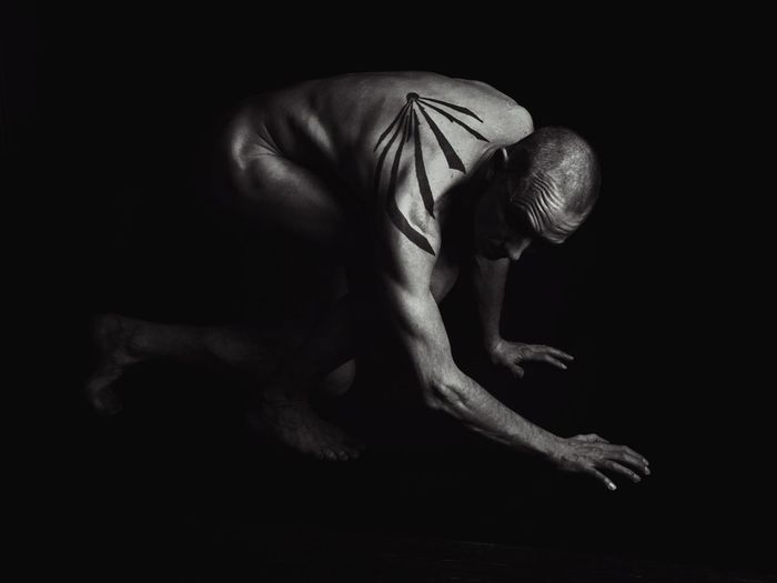 Side View Of Depressed Naked Man With Tattoo Bending Against Black Background