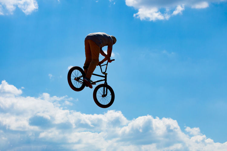 Low angle view of man with bicycle against sky