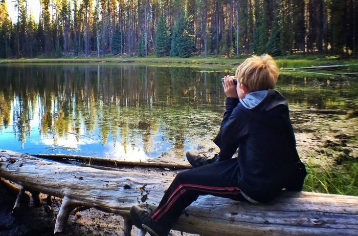 Watching birds at Teal Lake Sitting Casual Clothing Forest Leisure Activity Lake Relaxation Blond Hair Water Full Length Tranquility Tranquil Scene Day Tourism Person Nature Outdoors Non-urban Scene Loneliness Green Color Vacations My Son ❤