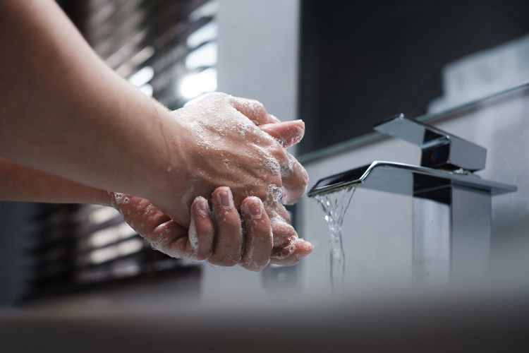 Cropped image of person washing hands at home