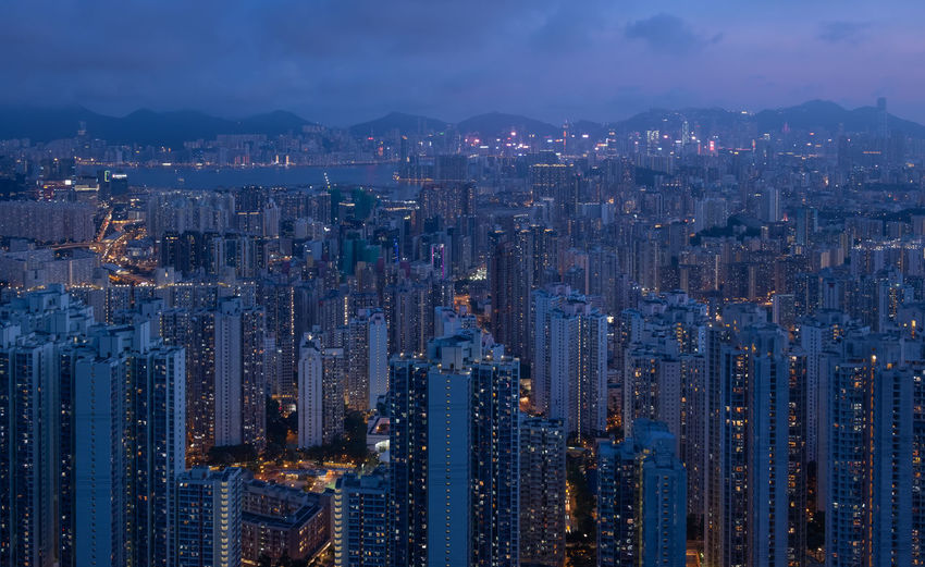 Aerial view of illuminated buildings in city against sky at night