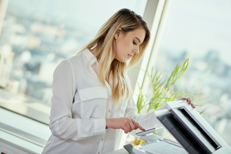 Young businesswoman holding documents using printer at office
