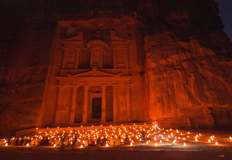 Low angle view of people sitting against illuminated building at night