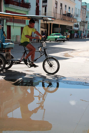 Been There. Cuba Havana, Cuba Havanna, Cuba Architecture Bicycle Building Exterior Built Structure Casual Clothing City Cuban Life Land Vehicle Men Mode Of Transport One Person Puddle Real People Reflection Sky Stationary Transportation Water
