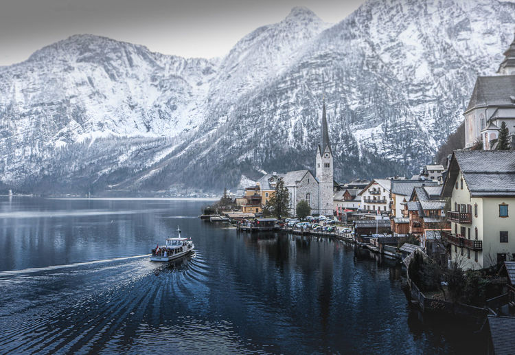 Scenic view of snowcapped mountains and building by lake