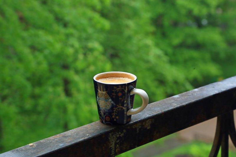 Close-up cup of coffee on railing against blurred background