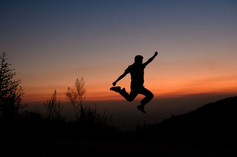 Silhouette man jumping against sky during sunset