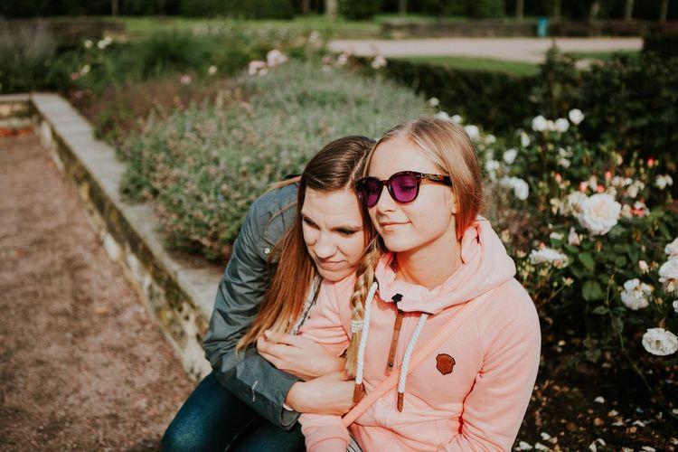 Portrait of two friends sitting in garden