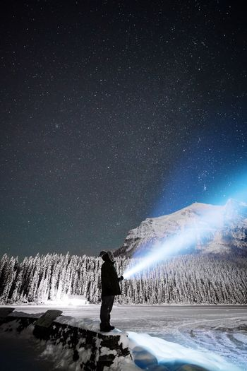 Man Standing By Frozen Lake Against Star Field At Night
