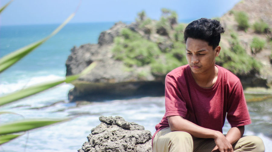 Young man looking away while sitting on rock by sea
