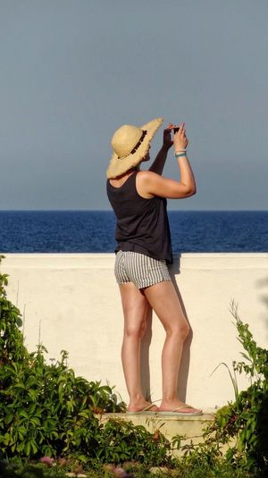 Woman Photographing Sea Through Mobile Phone