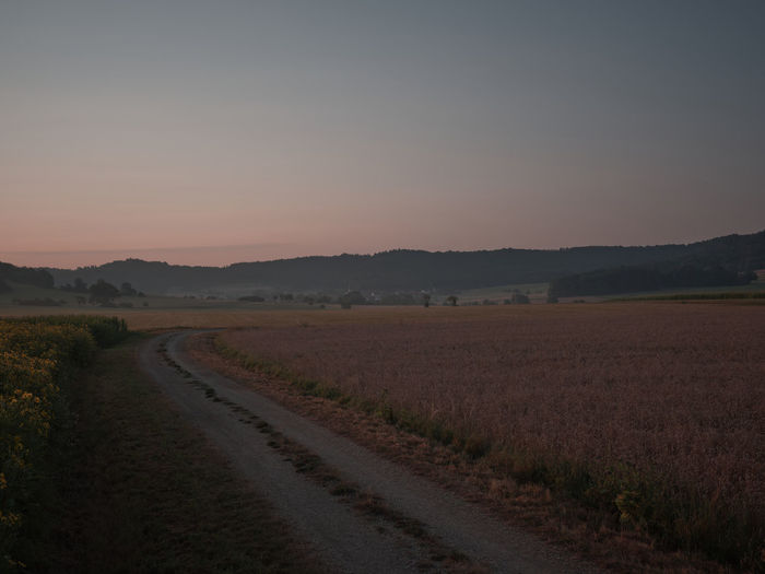 Empty road amidst field against clear sky during sunset