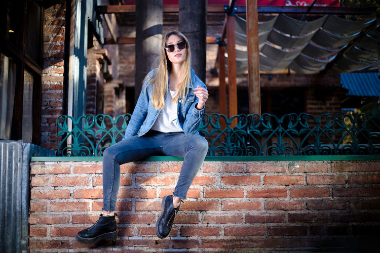 Portrait of young woman sitting against brick wall