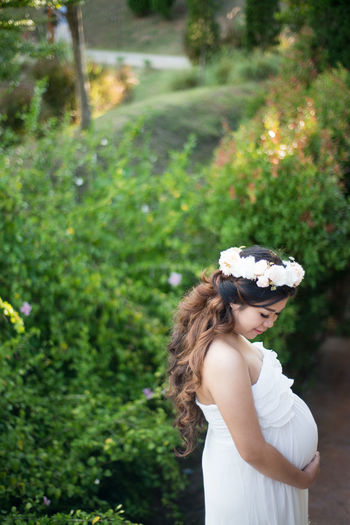 Side view of pregnant woman in dress wearing flower tiara by plants