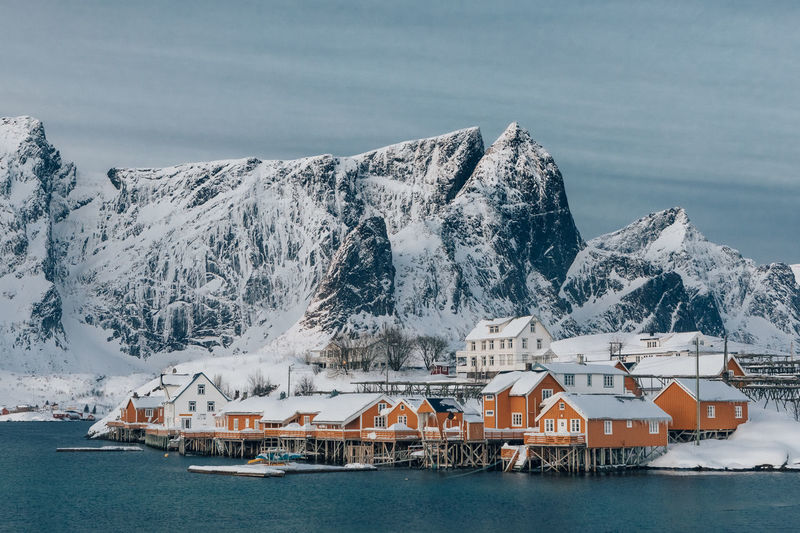 Buildings by sea against sky during winter