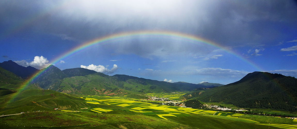 Green field and mountains with rainbow Beauty In Nature Cloud - Sky Day Double Rainbow Idyllic Landscape Mountain Mountain Range Multi Colored Nature No People Outdoors Rainbow Scenics Sky Spectrum Tranquil Scene Tranquility