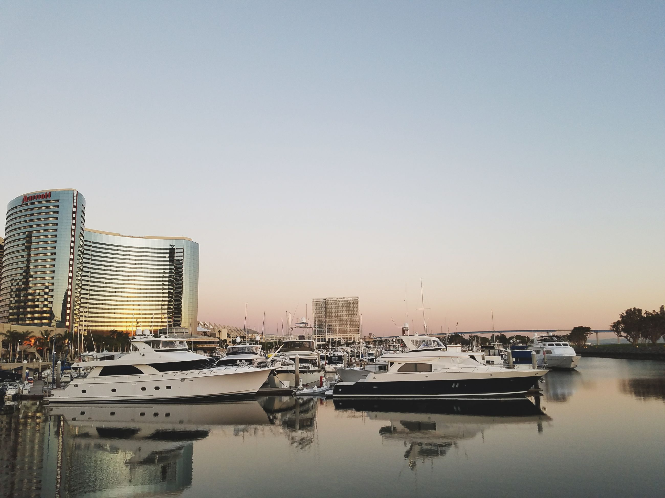 building exterior, clear sky, water, architecture, reflection, built structure, city, outdoors, no people, sky, waterfront, river, nautical vessel, cityscape, day, skyscraper, urban skyline, nature