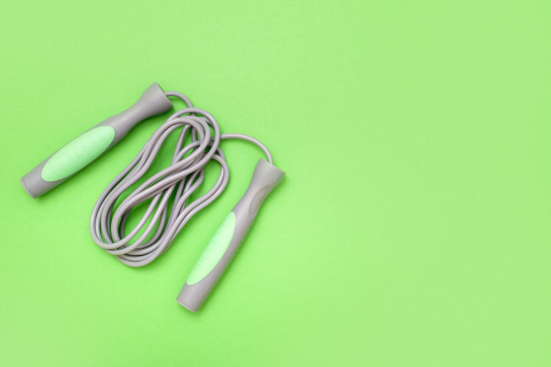 Jump rope on green background, top view Tool Lifestyle Cord Blue Handle Health Practicing One Equipment Closeup Workout Amusement  Care Hobby Object Athletic Sport Background Healthy Gym Top View Childhood Rope Isolated Exercise Skip Curve Strength Game Activity Jumping Training Modern Leisure Jump Toy Nobody Design White Children Fitness Play Studio Shot Colored Background Indoors  Still Life Copy Space Green Color Green Background Cut Out No People Directly Above Close-up Table High Angle View Variation Single Object Multi Colored Metal Office Supply Connection Two Objects