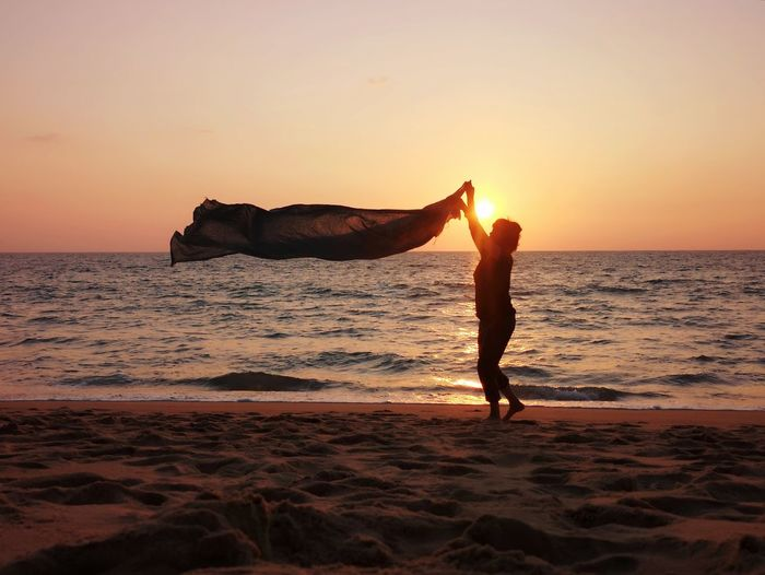 Side view of silhouette woman holding fabric while standing at beach against sky during sunset